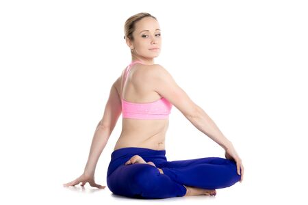 revolved: Sporty beautiful blond young woman sitting in variation of Lotus pose, parivrtta Ardha Padmasana, Revolved half lotus posture, stretching hips, knees, shoulders and spine, studio full length Stock Photo