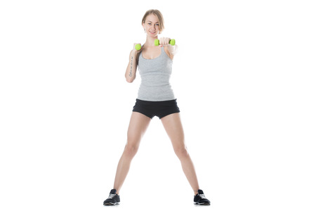 translated: Portrait of young slim cheerful attractive woman working out, doing weight training with dumbbells, French tattoo on her arm translated as What woman wants, God wants, studio, white background Stock Photo