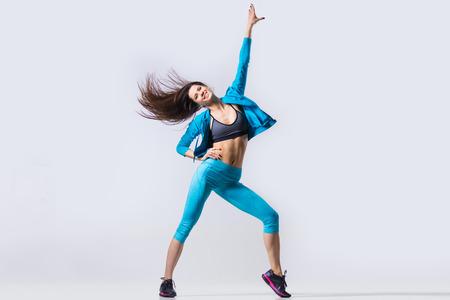 Een gelukkig lachend aantrekkelijke prachtige jonge fit moderne vrouw in blauwe sportkleding warming up, uit te werken, dansen met haar haren vliegen, volledige lengte, afbeelding studio op een grijze achtergrond