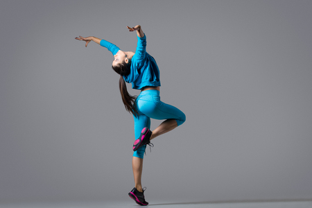 One attractive gorgeous young fit modern woman in blue sportswear with ponytail dancing, image in movement, full length, studio on gray background