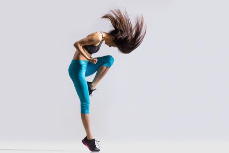 adentro y afuera: Una señora joven del ajuste hermoso moderno bailarina en ropa deportiva azul calentar, hacer ejercicio, bailar con ella la imagen de estudio a largo pelo suelto, de larga duración, sobre fondo gris