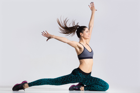 attractive gorgeous: One happy attractive gorgeous young fit modern woman in blue sportswear with ponytail working out, dancing, in movement with her hair flying, full length, studio image on gray background