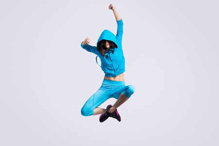 charming woman: One beautiful young fit modern dancer lady in blue sportswear hoodie sweater working out, dancing and jumping, full length, studio image on gray background