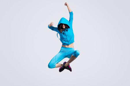 mujer alegre: Una señora joven del ajuste hermoso moderno bailarina en azul ropa deportiva suéter con capucha que se resuelve la imagen de estudio sobre fondo gris, bailar y saltar, de cuerpo entero,