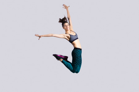 jumping: One happy attractive gorgeous young fit modern woman in aquamarine sportswear with ponytail working out, dancing, jumping with joy, full length, studio image on gray background