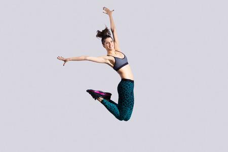 jumping: Una feliz mujer joven magnífica atractiva en forma moderna en ropa deportiva de color aguamarina con cola de caballo que se resuelve, bailando, saltando con alegría imagen del estudio, integral, sobre fondo gris