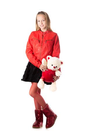 Portrait of happy beautiful casual teenage girl in red leather jacket holding teddy bear, friendly smiling, looking at camera with cheerful expression, isolated, studio, white background Stock Photo