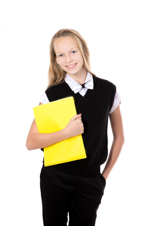 schoolgirl uniform: Portrait of happy cute beautiful blond schoolgirl wearing black formal outfit with bow tie, holding yellow folder, posing, friendly smiling, isolated studio shot, white background Stock Photo