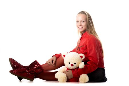 women in boots: Portrait of happy beautiful casual teenage girl in red leather jacket sitting with teddy bear, friendly smiling, looking at camera with cheerful expression, studio, white background, copy space