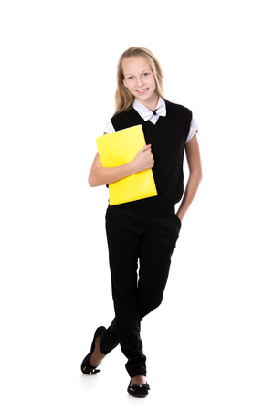 schoolgirl in uniform: Happy cute beautiful blond schoolgirl wearing black formal outfit with bow tie, holding yellow folder, posing, friendly smiling, isolated studio shot, white background, full length