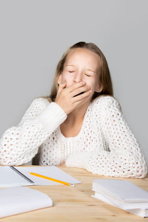 slacker: Portrait of sleepy funny beautiful casual girl, sitting at desk, yawning with closed eyes, tired or bored with hard school task, studio, gray background