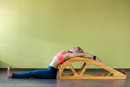 Portrait of sporty beautiful young blond woman in sportswear working out indoors, doing exercise for spine flexibility and correct posture on Viparita Dandasana backbend bench, full length