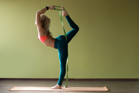 Portrait of sporty beautiful blond young woman in sportswear working out indoors, doing balance back bend, Natarajasana, Lord of the Dance posture, variation with belt on orange mat, full length