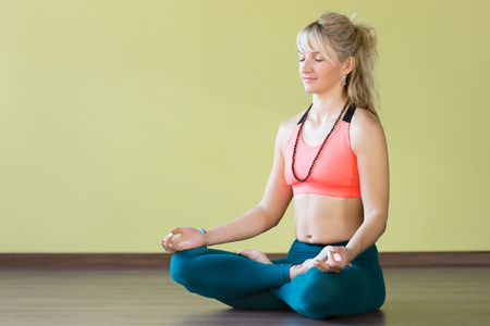 jnana: Sporty beautiful blond woman in sportswear working out indoors, sitting cross-legged in Padmasana, Lotus posture, asana for meditation, breathing exercises, fingers in Jnana mudra, full length