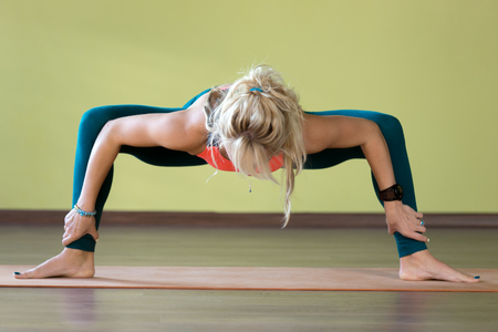 straddle: Sporty beautiful blond young woman in sportswear working out indoors, doing rudrasana (sumo), utkata konasana (goddess or temple posture) on orange eco mat, full length Stock Photo