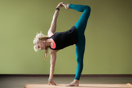 active life: Sporty beautiful blond young woman in sportswear working out indoors, doing variation of Half Moon Posture, Ardha Chandrasana, on orange eco mat, full length
