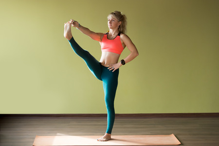 hasta: Sporty beautiful blond young woman in sportswear working out indoors, doing Utthita Hasta Padangushthasana, Extended Hand-To-Big-Toe yoga posture on orange eco mat, full length Stock Photo