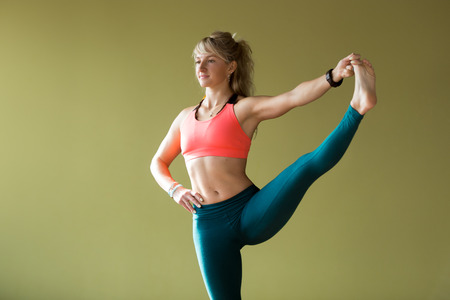 big toe: Portrait of sporty beautiful blond young woman in sportswear working out indoors, doing Utthita Hasta Padangustasana, Extended Hand To Big Toe yoga posture