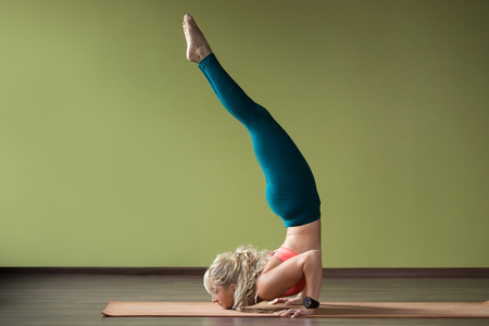 formidable: Sporty beautiful blond young woman in sportswear working out indoors, doing yoga chin balance Ganda Bherundasana, Formidable Face Posture on orange eco mat, full length Stock Photo
