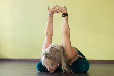 knee bend: Sporty beautiful blond young woman in sportswear working out indoors, doing variation of Padmasana, sitting cross-legged, bending forward in Lotus Posture, exercise for shoulders flexibility