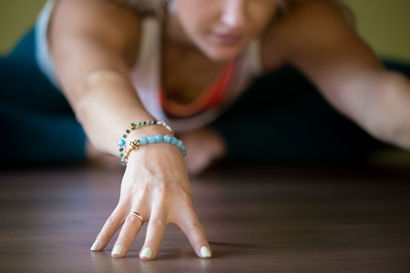 Sporty beautiful blond young woman working out indoors, doing Butterfly Pose, sitting in Purna Titli or Baddha Konasana Posture, full length, close-up, focus on hand Standard-Bild