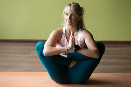 beautiful womb: Happy beautiful blond young woman in sportswear working out indoors, doing variation of Pranama Garbha Pindasana - Womb Embryo Pose with Namaste on orange eco mat, full length Stock Photo