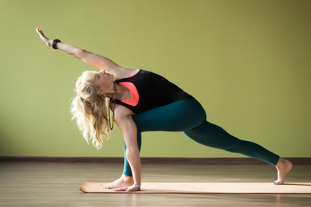 revolved: Sporty beautiful blond woman in sportswear working out indoors, doing lunge exercise for hips and spine flexibility, standing on orange eco mat in Parivrtta Parsvakonasana yoga pose, full length