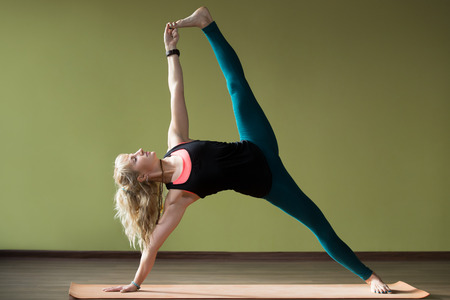 Portrait of sporty beautiful blond woman in sportswear working out indoors, doing advanced variation of Side Plank Posture, Vasisthasana on orange eco mat, strengthening arms, belly, legs, full length