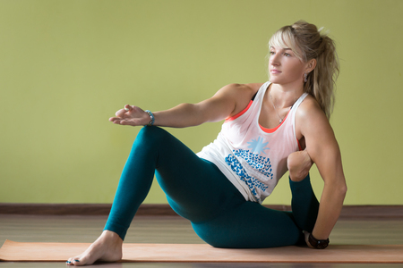 Sporty serene beautiful blond young woman in sportswear working out indoors, doing variation of Yoga Dandasana Posture on orange eco mat, full length