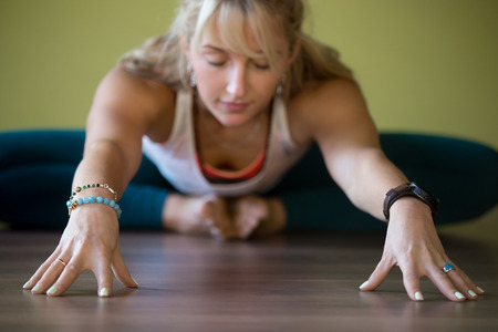 baddha: Sporty beautiful blond young woman in sportswear working out indoors, doing Butterfly Pose with closed eyes, sitting in Purna Titli or Baddha Konasana Posture, full length, close-up, focus on hands Stock Photo