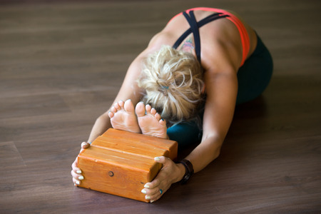 hamstrings: Sporty beautiful young blond woman in sportswear working out indoors, doing exercise for spine, shoulders, hamstrings, sitting in seated forward bend posture, focus on wooden bricks