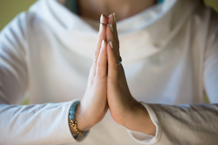 Close-up of hands of sporty young beautiful woman in white clothes meditating indoors, focus on arms in Namaste gesture