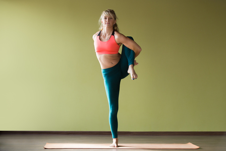 big toe: Sporty beautiful blond young woman in sportswear working out indoors, doing simple variation of Utthita Hasta Padangustasana, Extended Hand To Big Toe yoga posture on orange eco mat, full length