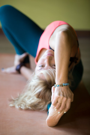 janu: Sporty beautiful blond young woman working out indoors, doing posture for strengthening and stretching shoulders, spine, groins, and hamstrings on orange mat, close-up, focus on arm grasping foot Stock Photo