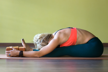 hamstrings: Sporty beautiful young blond woman in sportswear working out indoors, doing exercise for spine, shoulders, hamstrings, sitting in paschimothanasana pose, seated forward bend posture, using wood bricks Stock Photo