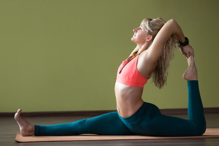 pada: Portrait of sporty beautiful blond woman in sportswear working out indoors, doing backbend, variation of Eka Pada Rajakapotasana (One-Legged King Pigeon Posture) on orange eco mat, full length