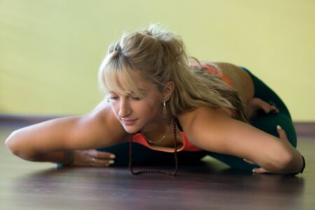 knee bend: Sporty beautiful blond young woman in sportswear working out indoors, doing variation of Padmasana, sitting cross-legged, bending forward in Lotus Posture, full length
