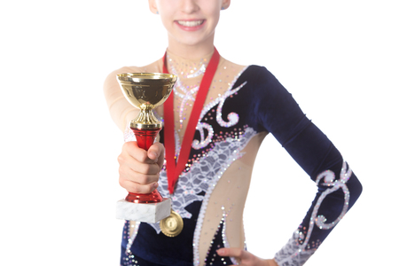 gimnasia ritmica: Portrait of beautiful happy smiling fit gymnast or skater young woman in sportswear posing with golden cup and first place medal, close-up, focus on the goblet, studio, isolated, white background Foto de archivo