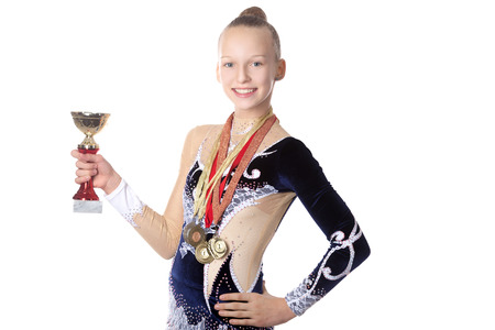 Portrait of beautiful happy smiling cool fit gymnast or skater young woman in sportswear dress posing with golden cup and first place medals, studio, isolated, white background