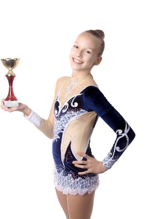 gymnastique: Portrait de la belle souriante gymnaste fra�che ajustement heureux ou patineur jeune femme en robe de v�tements de sport posant avec d'or d'abord tasse, studio, isol�, fond blanc Banque d'images