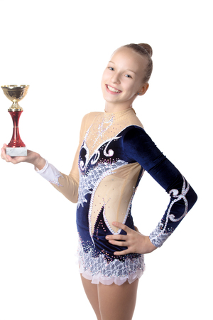 gimnasia ritmica: Retrato de la sonrisa hermosa gimnasta fresca ajuste feliz o mujer joven patinador en traje de ropa deportiva que presenta con la primera taza de oro lugar, estudio, aislado, fondo blanco