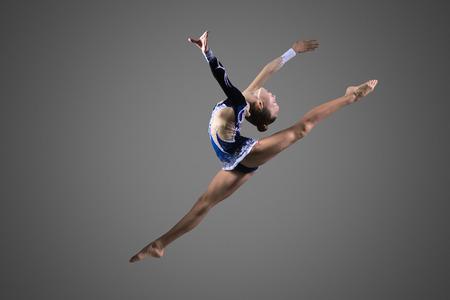 estiramientos: ajuste joven gimnasta fresca hermosa en vestido azul elaboración de ropa deportiva, realizando elemento de gimnasia de arte, saltando, haciendo salto dividir en el aire, el baile, de cuerpo entero, estudio, fondo oscuro