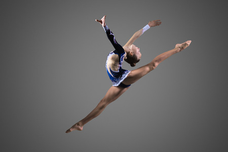 Beautiful cool young fit gymnast woman in blue sportswear dress working out, performing art gymnastics element, jumping, doing split leap in the air, dancing, full length, studio, dark background