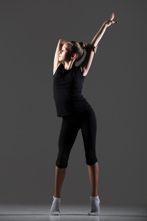 tiptoes: Beautiful cool young fit gymnast athlete woman in sportswear working out, dancing, doing art gymnastics, standing on tiptoes, full length, studio, dark background