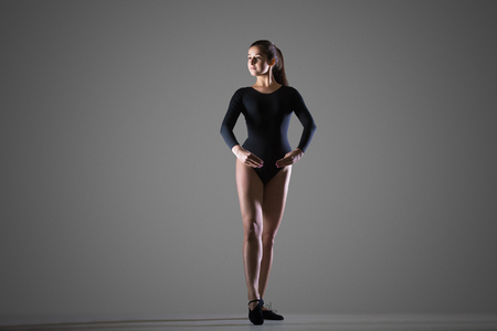sports clothing: Beautiful young dancer woman in black sportswear working out, dancing, full length, studio, dark background