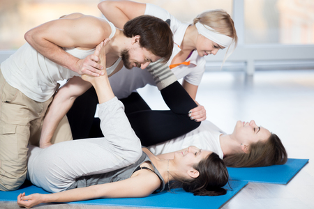 yoga class: Fitness, stretching practice, group of four beautiful cheerful fit young people working out in sports club, doing exercises for hips flexibility on blue mats, partners helping to deepen pose