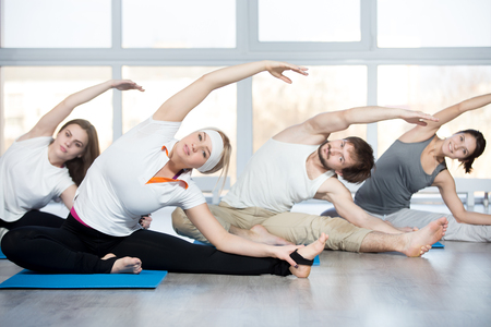 janu: Fitness, stretching practice, group of four beautiful happy fit young people working out in sports club, doing side bend exercise, Revolved Head to Knee pose on blue mats in class
