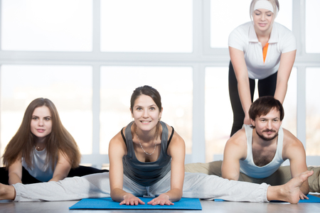 straddle: Fitness, stretching practice, group of three beautiful happy fit young people working out in sports club, doing Seated straddle posture on blue mats, instructor helping student to correct the pose