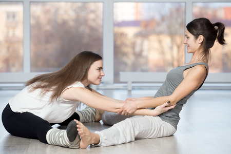 straddle: Fitness, stretching practice, group of two beautiful happy fit young people working out in sports club, instructor helping student to do Seated straddle posture, Upavishtha Konasana Stock Photo