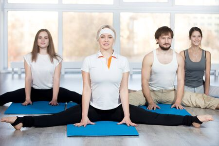 Fitness, stretching practice, group of four beautiful happy fit young people working out in sports club, doing easy variation of Wide-Angle Seated Forward Bend pose on blue mats in class